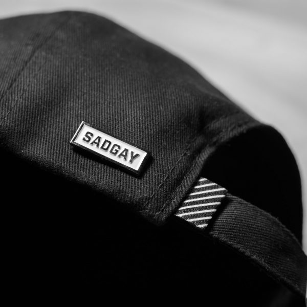 Sadgay pin on the side of a black hat