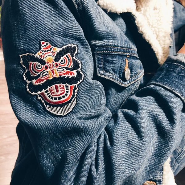 Lion dance patch on the arm of a jean jacket