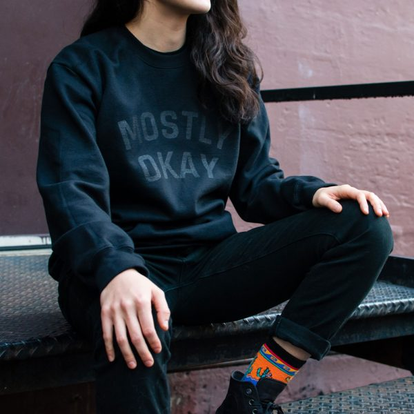 A person wearing a mostly okay sweater sitting on metal stairs