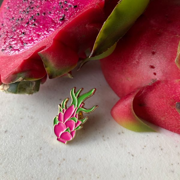 Dragonfruit pin in front of a cut up red fleshed dragonfruit