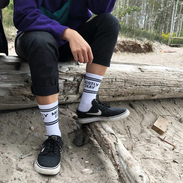 "Person sitting on a tree trunk on the beach. The focus on the photo is on the white crew socks they are wearing that say ""Mostly Okay"""