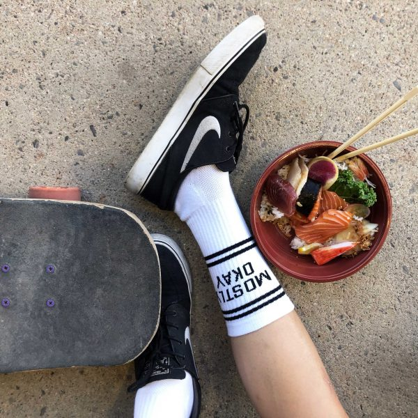 "A shot of a persons lower leg wearing white crew socks with the words ""Mostly Okay"" on them. Beside is a skateboard and a bowl of chirashi"