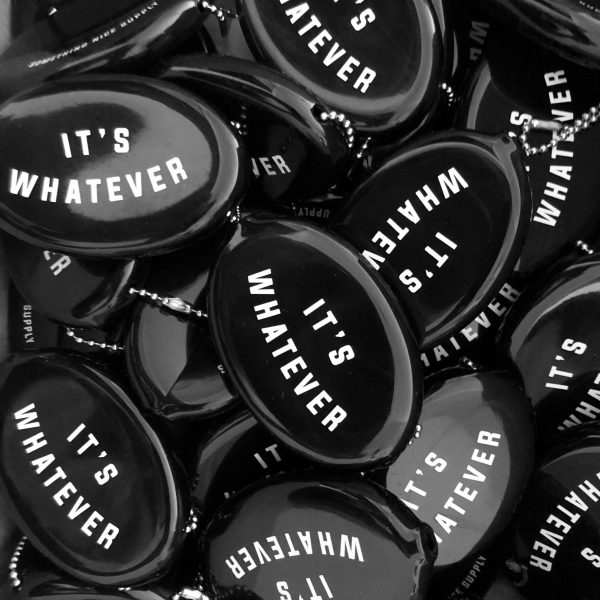 "A pile of black rubber coins pouches that have the statement ""It's Whatever"" on them."