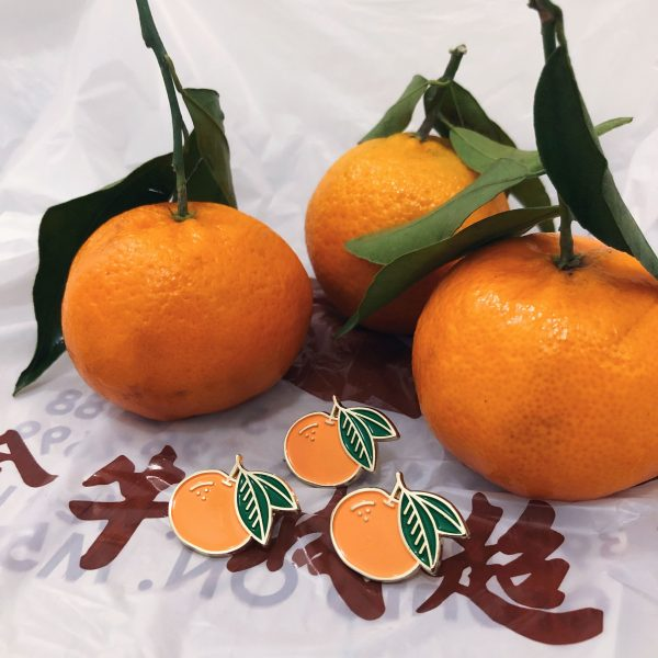 Close up of 3 mandarin orange enamel pins in front of 3 real mandarin oranges